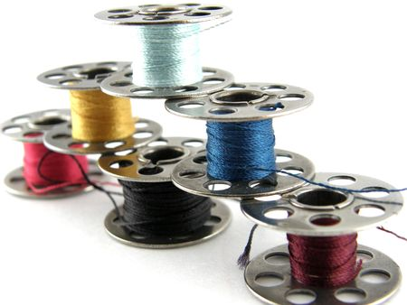 Bobbins of vibrantly colored thread isolated on white