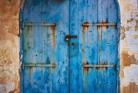 Old blue wooden rustic painted door in the countryside with metal hinges with rust