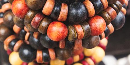 Coloured artisan wooden bead bracelets on display as ethnic jewellery Archivio Fotografico
