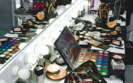 Rabat / Malta - December 8 2019: Makeup products, accessories and tools on a salon table in front of a light mirror