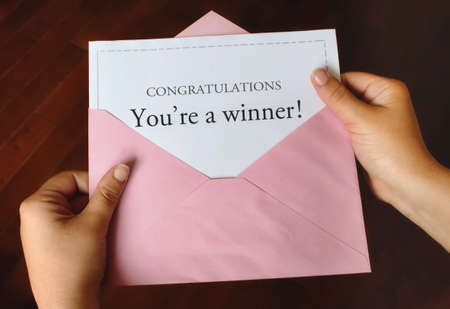 A letter that says Congratulations You're a winner! with female hands holding the open pink envelope