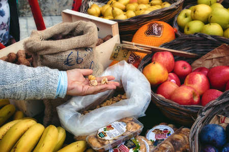 Market vendor cart with varied fruit in wicker baskets and sacks Archivio Fotografico