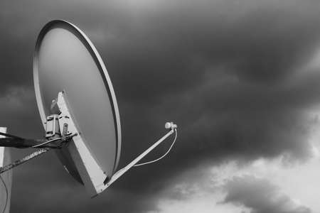 Black and white satellite dish on a rooftop against a cloudy moody sky background