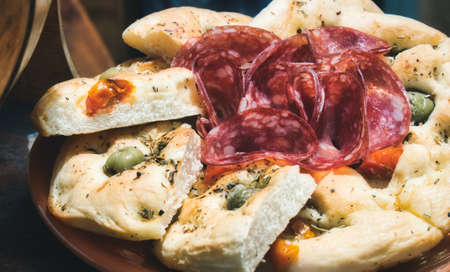 Plate of focaccia bread with slices of salami and olives