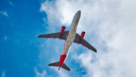 Underbelly of a jet airplane flying in the air isolated against a blue sky with clouds