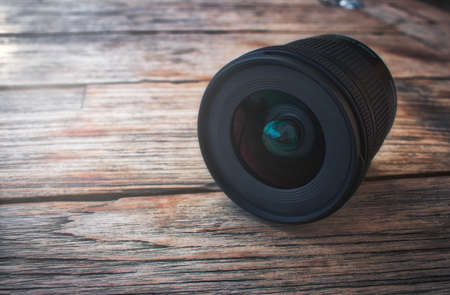 Camera lens on a rustic wooden table with soft light