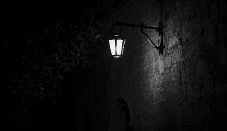 Spooky black and white alley with a lit street lamp Stockfoto