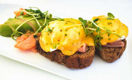 Eggs Benedict on brown bread toast with smoked salmon and sliced avocado Foto de archivo