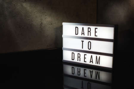 Dare to dream motivational message on a light box in a cinematic moody background