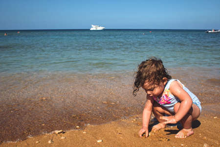 Little girl playing on a sandy beach by the sea