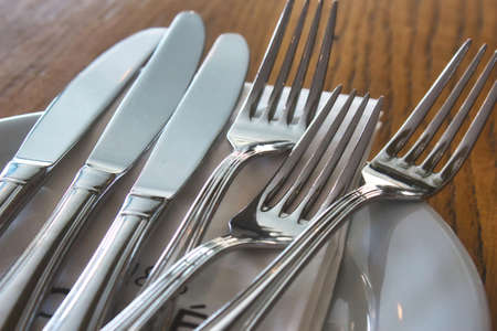 Shiny cutlery (knives and forks) and a ceramic plate on a table in a restaurant Stok Fotoğraf