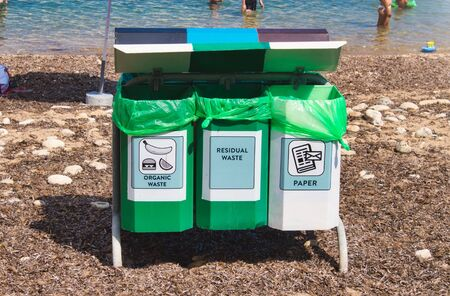 Recycling bins on a public natural beach