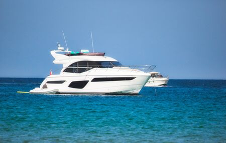 A luxury yacht sailing on the sea with clear blue sky and horizon visible in the background