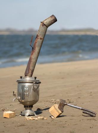 samovar and a hatchet on the wet sand near river photo