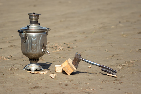 samovar and a hatchet on the wet sand photo