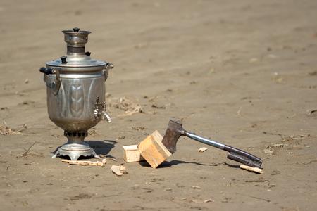 samovar and a hatchet on the wet sand photo