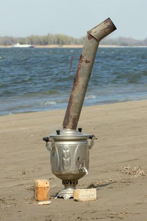 samovar on the wet sand near river photo