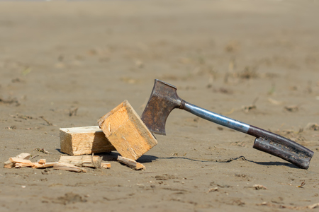 hatchet: hatchet and wood chips on the wet sand Stock Photo