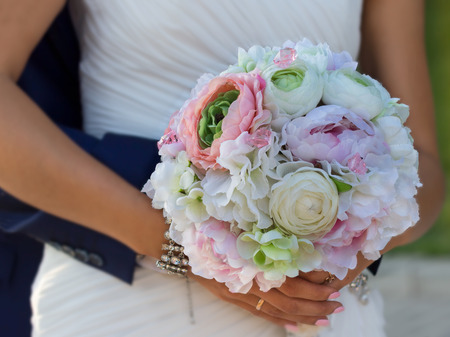 bouqet: flower bouqet in hands of bride which groom embracing