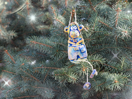 monkey on a tree: merry monkey from clay pottery sits on the tree among the stars. Holiday concept for New Years