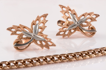 embellished: gold chain and gold earrings in the form of maple leaves embellished with platinum Stock Photo