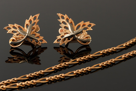 embellished: gold necklace and earrings in the form of maple leaves embellished with platinum Stock Photo