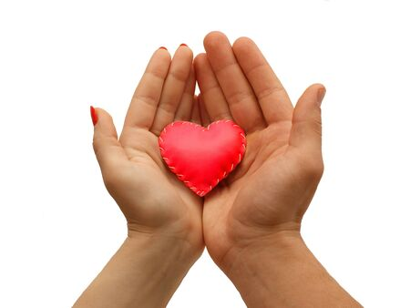 solicitude: womans hand and mens hand together   hold a red heart, isolated  on white background