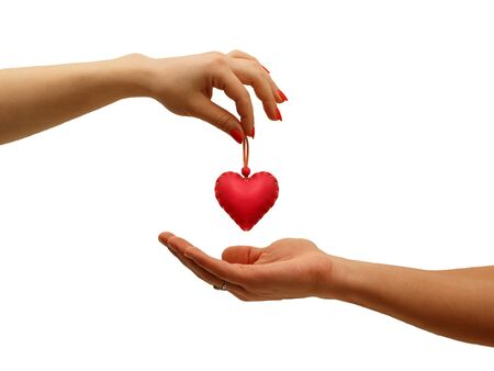 solicitude: closeup girls hand giving red heart in hand man, isolated on white Stock Photo