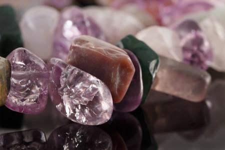 fluorite: closeup crystals of amethyst, fluorite, jasper and rose quartz on black table. Selective Focus