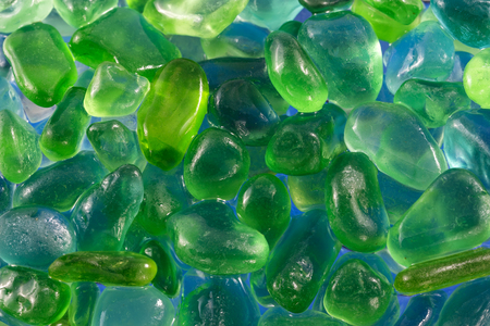 machined: close up of green and blue pebbles on a sea shore or river bed Stock Photo