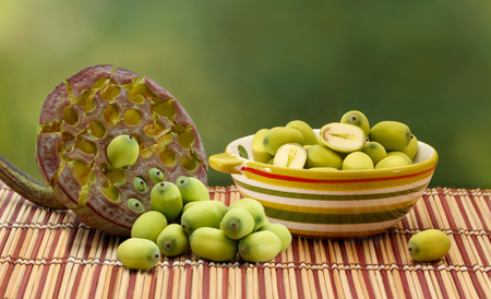 aquatic herb: Fresh green lotus seed (lotus nut) in ceramic bowl and lotus seed box on green background Stock Photo