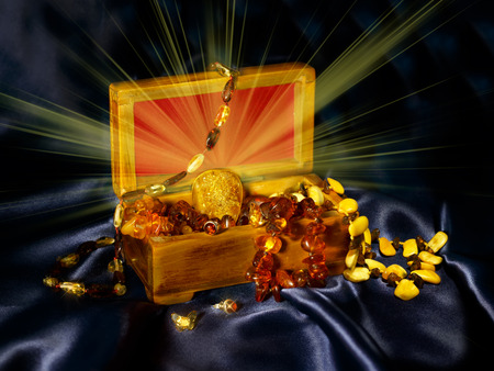 magnificence: Old wooden chest with a bunch of jewelry from authentic Baltic amber with a brilliant pendant in the center , on a blue background satin. Stock Photo