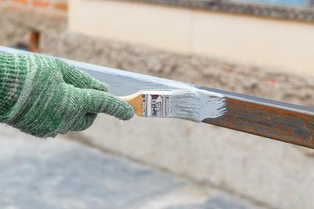 Rechte Hand in Lappen Handschuh Pinsel Stahl Pfosten in grau Anti Rost Farbe.