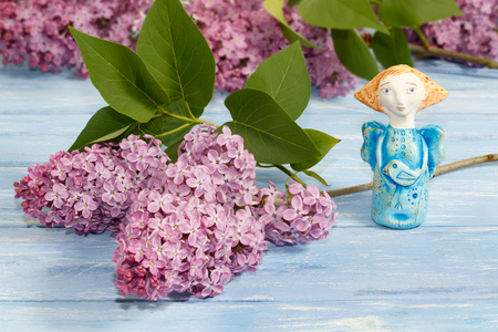 Töpfchen Engel aus Lehm und Zweige der Flieder auf alten blauen Holztisch