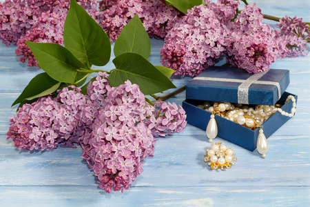 pearl jewelry in blue box and branches of lilac on old blue wooden table