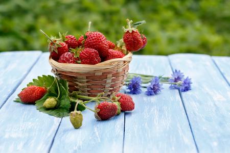 Closeup Erdbeere in Weidenkorb und blauen Kornblumen auf Holz blau Tisch auf einem Hintergrund von Laub