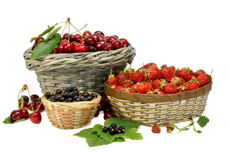 Summer gifts: cherries, strawberry and black currant in wicker baskets isolated on white.