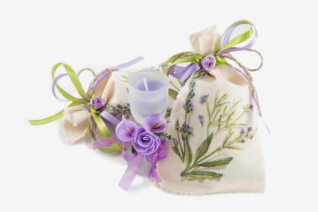 Zwei handgemachte Leinensäcke und Aromakerze im Glas verziert mit künstlichen Blumen auf weißem Hintergrund. Standard-Bild