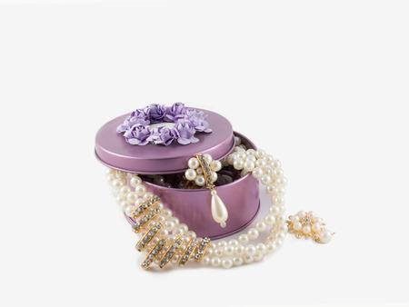 goldene Ohrringe und Halskette der schönen herrlichen Perle im violetten Edelsteinkasten auf weißem Hintergrund.