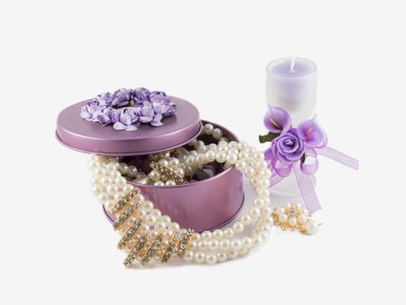 wunderschöne prächtige goldene Ohrringe in violetter Edelsteinbox, Aromakerze aus Glas mit künstlichen Blumen und Leinensack. auf weißem Hintergrund. Standard-Bild