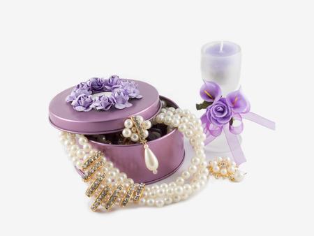 schöne wunderschöne goldene Ohrringe in violettem Edelsteinkasten und Aromakerze im Glas verziert mit künstlichen Blumen. auf weißem Hintergrund.