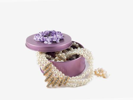 schöne Brosche der Nahaufnahme und herrliche Perlenhalskette im violetten Edelsteinkasten auf weißem Hintergrund.