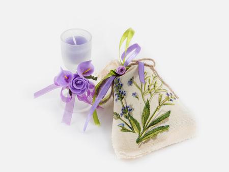 Handgemachte Leinensack- und Aromakerze im Glas verziert mit künstlichen Blumen auf weißem Hintergrund.