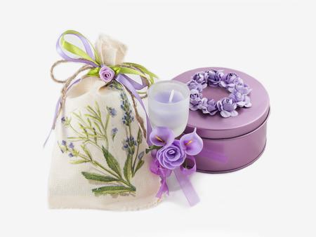 violetter Edelsteinkasten, Aromakerze im Glas verziert mit künstlichen Blumen und Leinensack auf weißem Hintergrund.