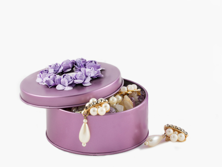 jewerly: closeup beautiful gorgeous golden earrings in violet gemstone box on white background.