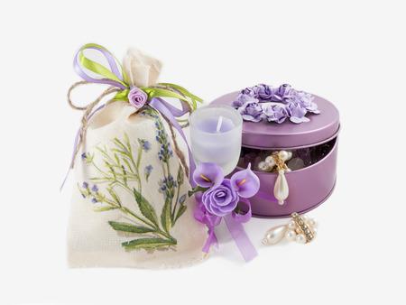 schöne wunderschöne goldene Ohrringe in violetter Edelsteinschachtel, Aromakerze im Glas mit künstlichen Blumen und Leinentasche verziert. auf weißem Hintergrund.
