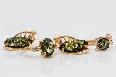 Nahaufnahmeschmucksadesatz goldene Ohrringe und Ringe mit authentischem natürlichem baltischem Grünbernstein auf Acryloberfläche auf weißem Hintergrund. Standard-Bild