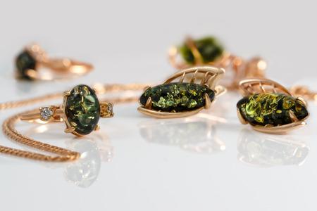 Goldener Ring und Ohrringe der Nahaufnahme mit authentischem natürlichem baltischem grünem Bernstein auf Acryloberfläche auf Hintergrund des Anhängers und des Ringes. kleiner DoF-Fokus