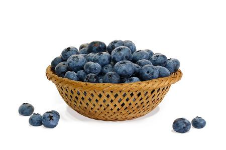 Blaubeere im Weidenkorb und kleine Stapel auf dem weißen Hintergrund lokalisiert Standard-Bild