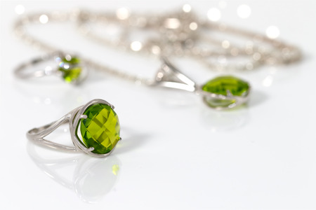 jewelle: Beauty silver ring with peridot on background pendant and ring on white acrylic desk. Stock Photo
